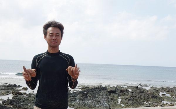 海辺で安納芋を持つ濱川農園園主濱川さん